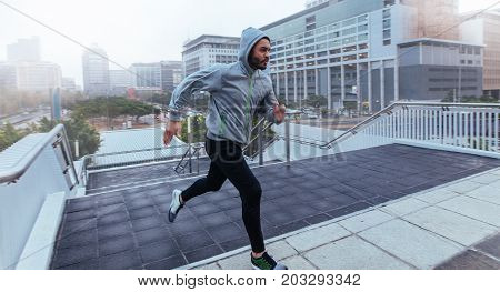 Man running up the stairs of a building during workout. Male athlete in hooded sweatshirt running in the city.