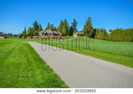 Road going through rural landscape with farmer's house on the hill
