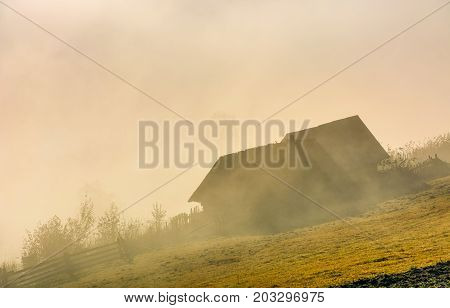 Abandoned Barn On Hillside In Fog At Sunrise