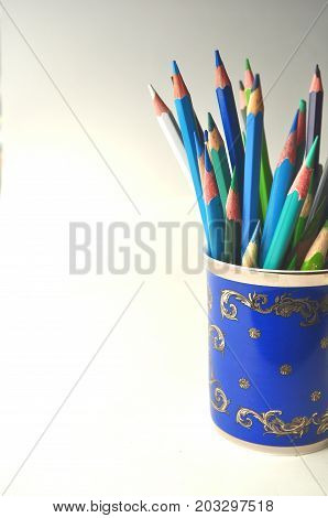 Styled stock image of blue and green color pencils in a blue china cup on grey with copy space