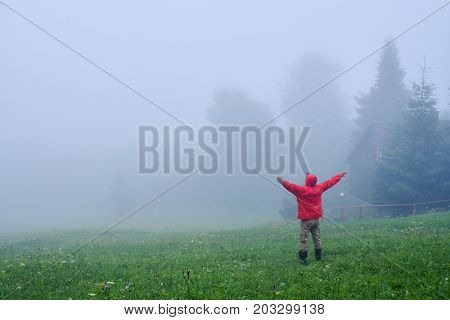 Rear view of male with outstretched hands in fog. Morning in Carpathian