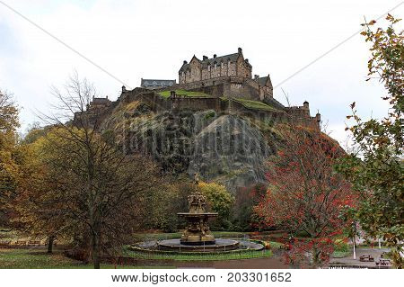 View of Edinburgh Castle and fountain on a cloudy day from Princes Street Garden in the early winter with autumn foliage.