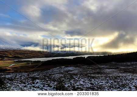 Beautiful snowy sunset with view of the Paps of Jura and Loch in the Scottish Highlands.