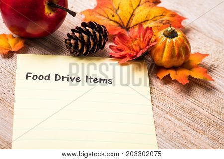 Fall Food Drive Items list concept on notebook and wooden board
