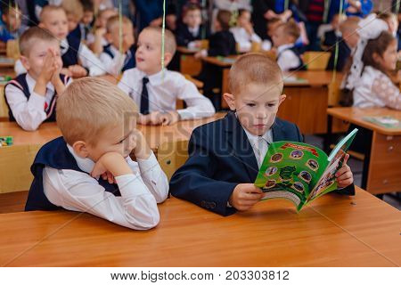 NOVOKUZNETSK, KEMEROVO REGION, RUSSIA - SEP, 1, 2017: First-grade students and teacher are in school classroom at first lesson. The day of knowledge in Russia.