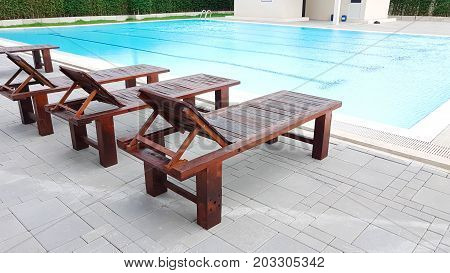 Brown Wooden Foldable Bed Beside The Swimming Pool