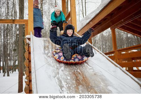 Three children play and ride snow tube on wooden slide covered with snow on winter day.