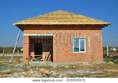 New Roof Membrane Coverings with Wooden Construction Home Framing with Roof Rafters Outdoor against Blue Sky. Roofing Construction Exterior with Red Brick house Wall Facade.