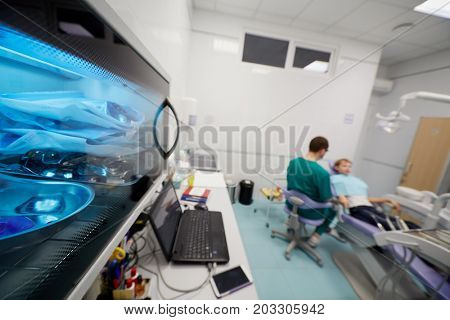 View of dentist office with doctor, patient and equipment, shallow dof.