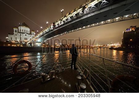 Man sails on ship in Moscow under Patriarchal bridge near Cathedral of Christ Savior at night