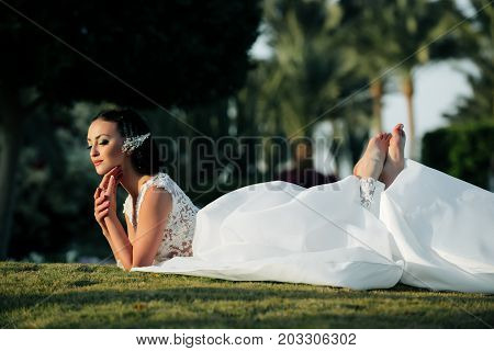 Woman lying on green grass on tropical landscape. Girl in white wedding dress. Bride with jewelry hairpin in brunette hair. Beauty and fashion concept. Summer vacation and honeymoon.