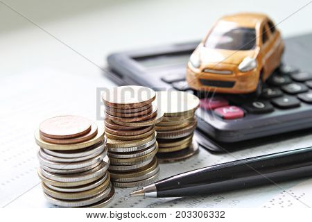 Business, finance, saving money, banking, loan, investment, taxes or accounting concept : Coins stack, pen and calculator on saving account book or financial statement
