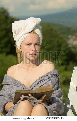 Student sunbathing on sunny day on natural background. Girl in bathrobe and towel on head. Summer holidays and vacation. Spa and wellness concept. Woman reading book on bench.