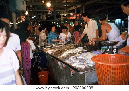 SINGAPORE / CIRCA 1990: Shoppers buy very fresh seafood at an indoor market.