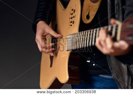 Close up of woman showing how to play guitar chord with copy space