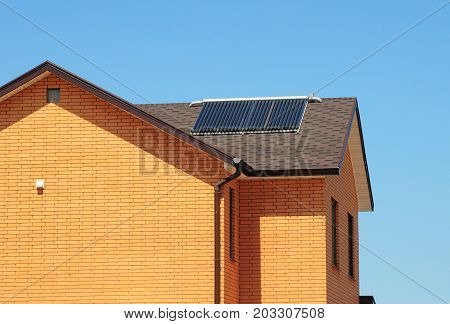 Vacuum collectors - solar water heating systemvents rain gutter on bitumen roof of the house