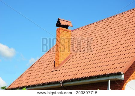 Faded red metal roof tile rain gutter and chimney against blue sky. Bad roofing.