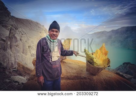 Kawah Ijen Volcano East Java Indonesia - August 132017: Sulfur miners carries sulfur from inside the crater of Kawah Ijen volcano in East Java Indonesia.