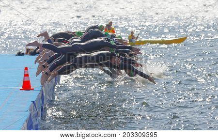 STOCKHOLM - AUG 26 2017: The female swimming competitors wearing black swimsuits jump into the water after the start signal in the Women's ITU World Triathlon series event August 22 2017 in Stockholm Sweden