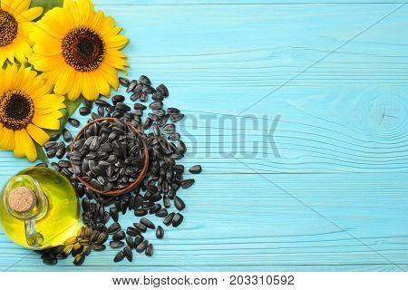 Sunflower Oil, Seeds And Flower On Blue Wooden Background. Top View With Copy Space