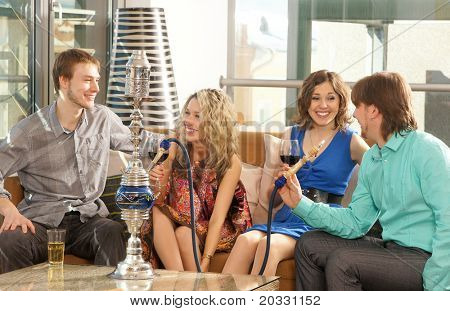Group of young and sexy people smoking hookah in the lounge caffee