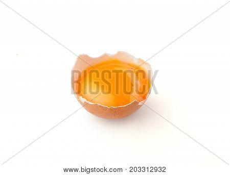 Yolk in the broken eggshell on the white background