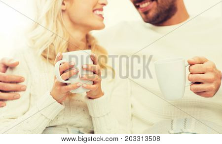 winter, love, family and happiness concept - close up of happy couple with tea cups at home