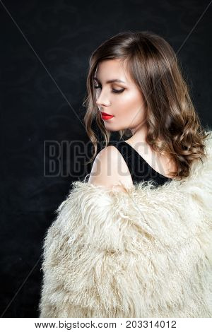 Beautiful Woman Fashion Model with Makeup and Curly Bob Hair. Fashionable Girl wearing Autumn or Winter Fur Coat and Evening Dress