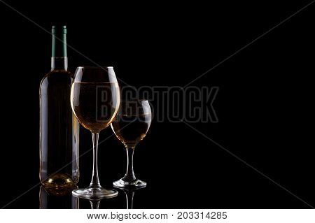 A bottle of white wine and two glasses with white wine on a dark background. Still life.