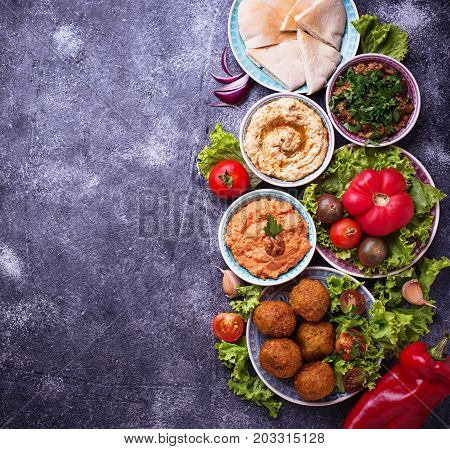 Selection of Middle eastern or Arabic dishes. Falafel, hummus, pita and  muhammara. Top view