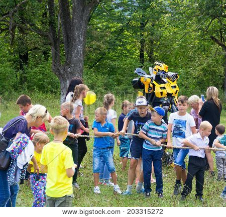 Adygea Russia - September 2 2017: children have fun and play with an animator in a transformer costume