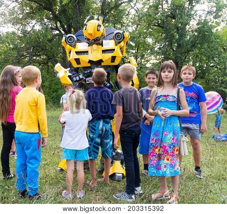 Adygea Russia - September 2 2017: children have fun and play with the animator in costume transformer bumblebee