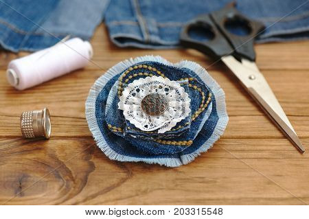Blue flower brooch or hair accessory. Scissors, thread, thimble, needle, old jeans on a wooden table. Recycle jeans projects. What to do with old blue jeans. Cheap crafts to make. Closeup