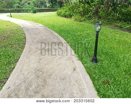 The way in garden. Concrete walkway on green grass field.