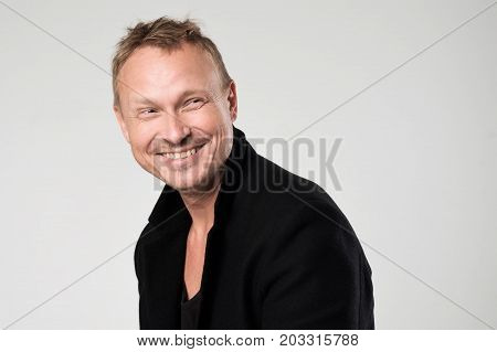 Smiling young man in black clothesstanding against white background Concept of self confident man. Positive man emotion