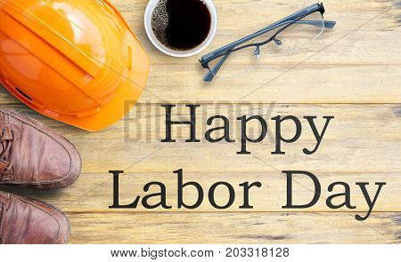 Labor Day is a federal holiday of United States America. Top view with orange safety helmet brown leather shoes and cup of coffee on old wooden table background. Space for use and any design.
