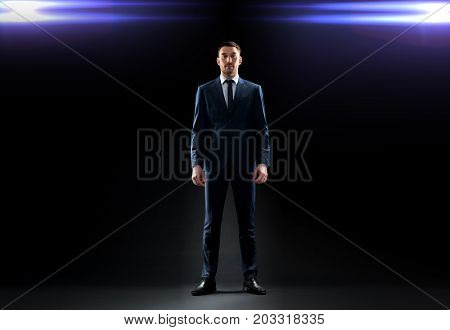 business, technology and people concept - businessman in suit over black background with laser light
