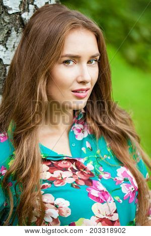 Young happy brunette woman in flowers blouse in the summer park