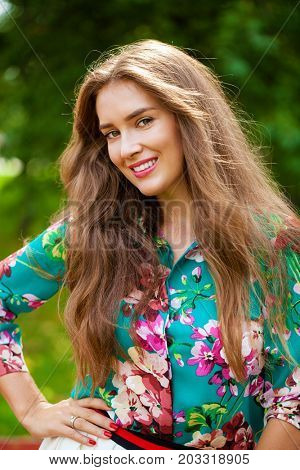Young happy brunette woman in white skirt and flowers blouse in the summer park