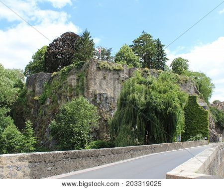 View of the ruins of the medieval Chateau Fresnay, from the bridge over the River Sarthe in Fresnay-sur-Sarthe in France.