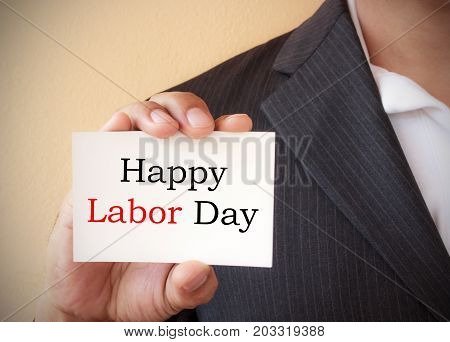 Close up a man wearing a suit showing a signboard with the text happy labor day written in it
