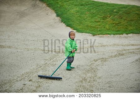 boy walking the golf course with a rake