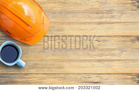 Top view with orange safety helmet and cup of coffee on old wooden table background. space for use and any design. Business and labor day concept.