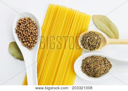 Various spices oregano, coriander seeds, bay leaves, cumin seeds and spaghetti