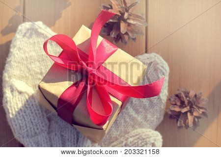 festive gift and warm mittens on the background of a table with spruce cones top view / warming surprise for Christmas