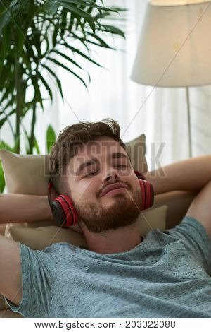 Smiling young man listening to his favorite song