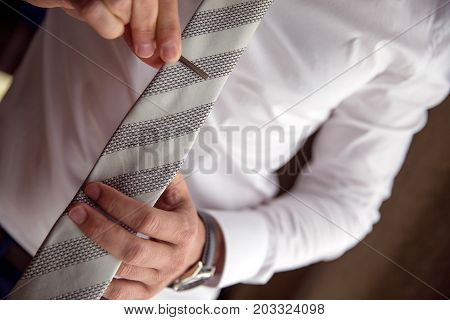Man clipping a necktie with a tie bar close up lifestyle detail shot.