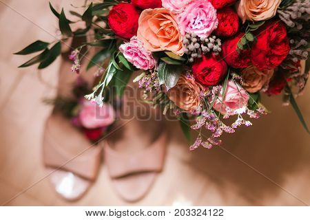 bridal bouquet posy with wedding shoes. Flowers in focus