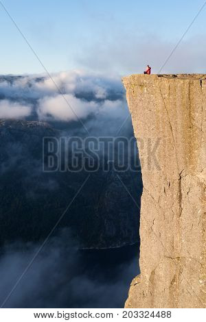 Preikistolen - amazing rock in Norway. Girl sitting on a cliff above the clouds. Pulpit Rock, the most famous tourist attraction in Ryfylke, towers over the Lysefjord