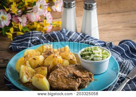 Braised Meat In Sauce Served With Boiled Potatoes.